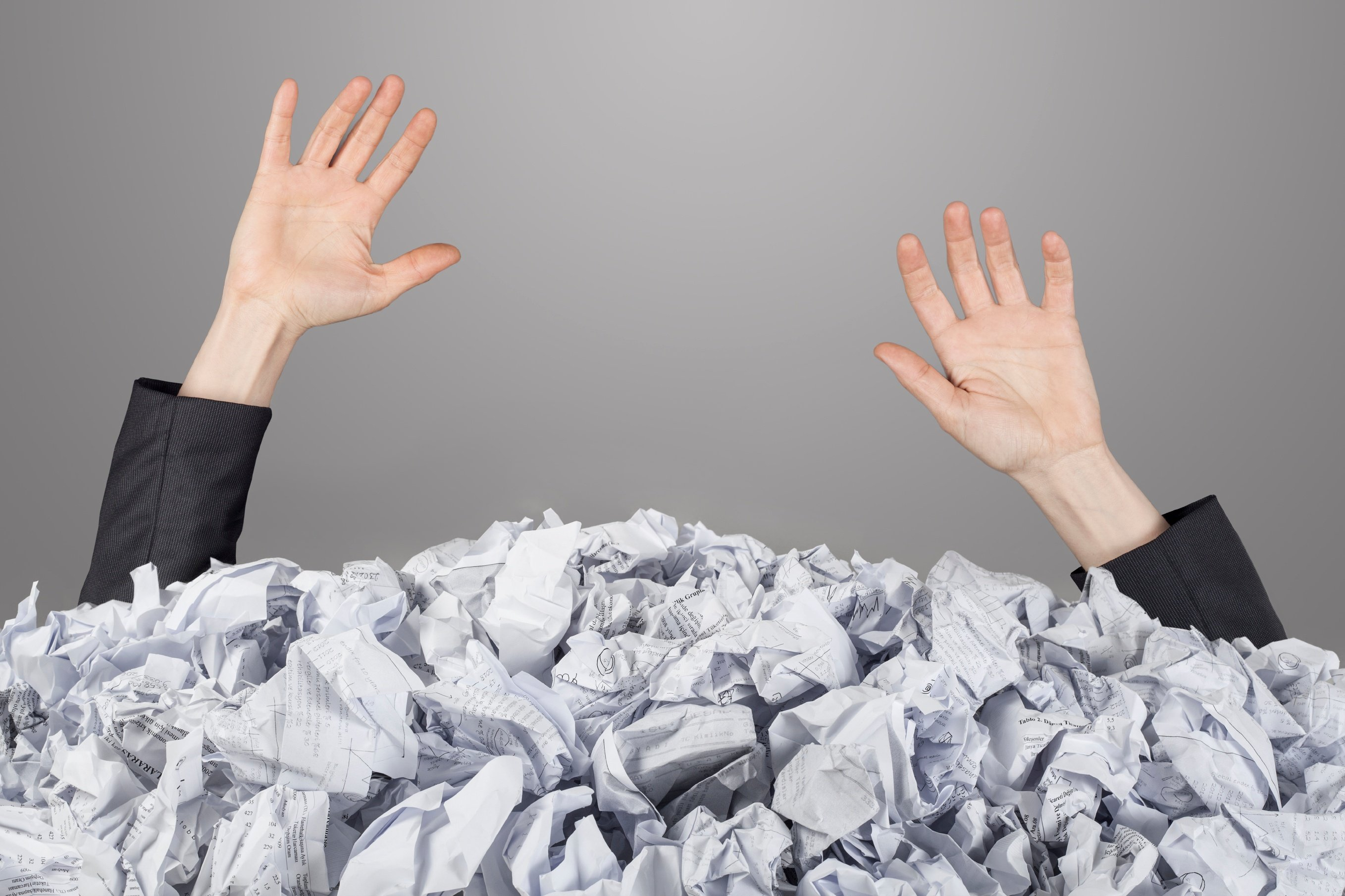Hands-reach-out-from-big-heap-of-crumpled-papers-000023637922_Large.jpg