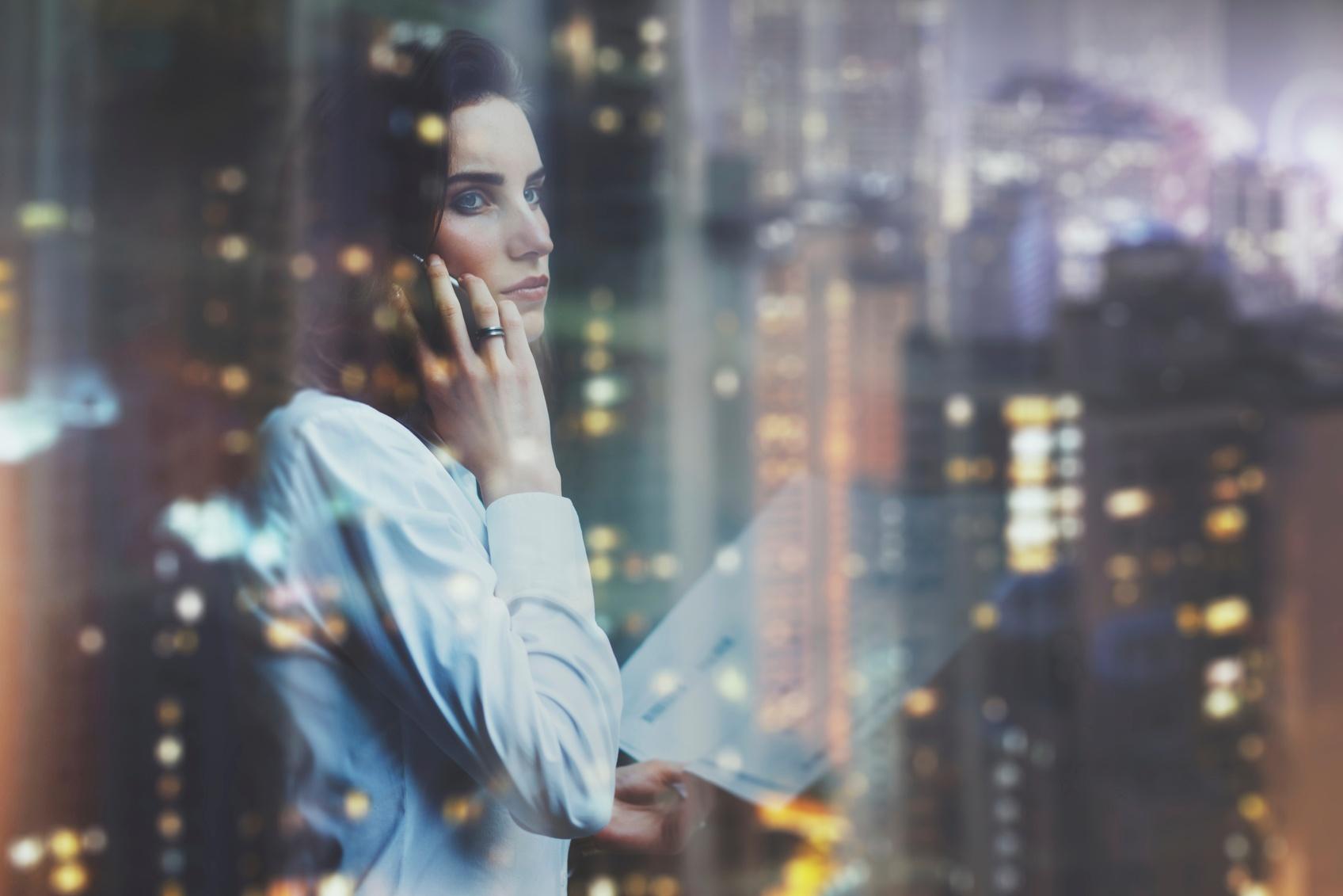 Photo-woman-wearing-white-shirt-talking-smartphone-and-holding-business-000089979727_Medium.jpg