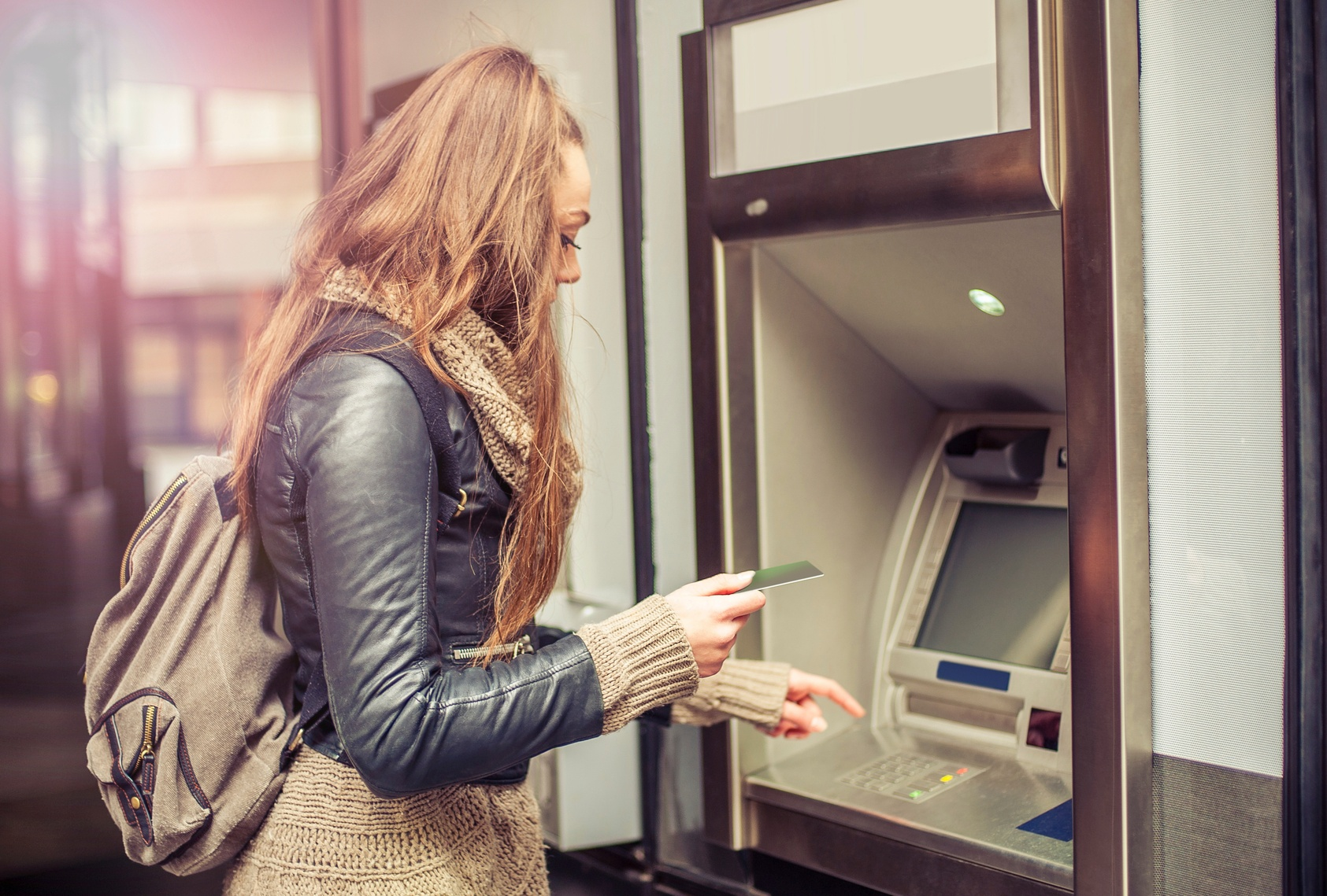 Young-woman-taking-money-from-ATM-000090495725_Medium.jpg